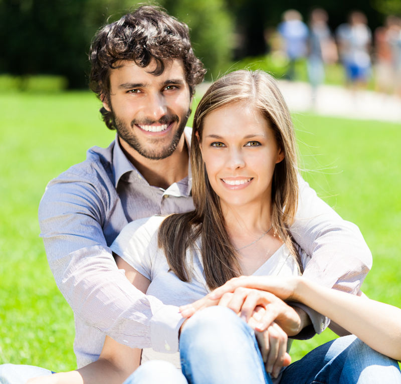 Young couple outdoors in sunshine with smiles.
